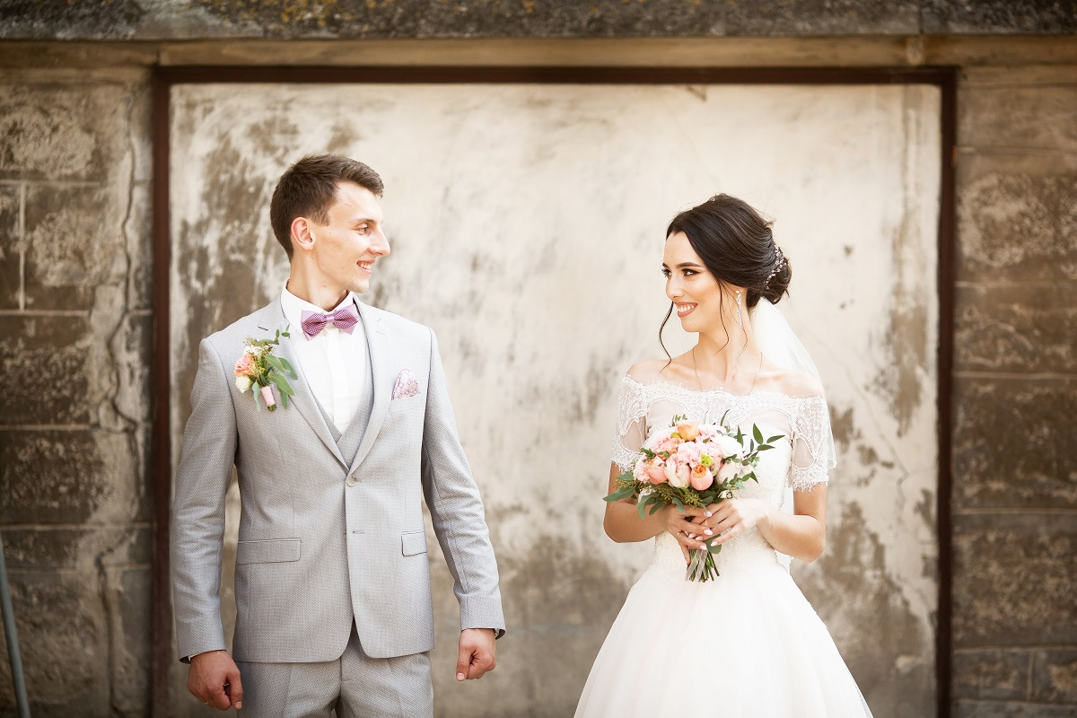 Contemporary bride and groom against whitewashed old brick wall
